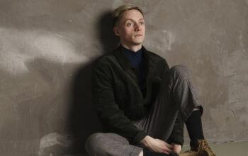 Singer Hamish Hawk sitting against a wall